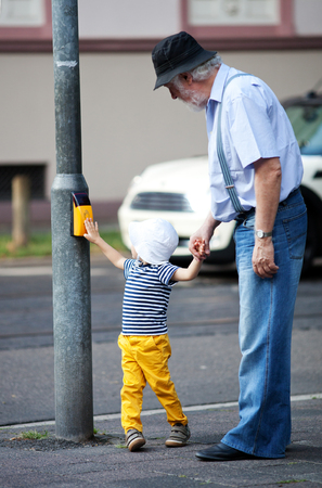 Grandfather and grandson crossing the street at the crosswalk