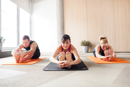 Three people in a yoga class holding a pose 免版税图像