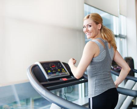 Jeune femme exerçant sur tapis roulant Banque d'images