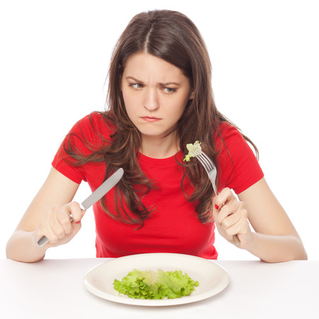 Displeased young woman eating green leaf lettuce, isolated on white 免版税图像