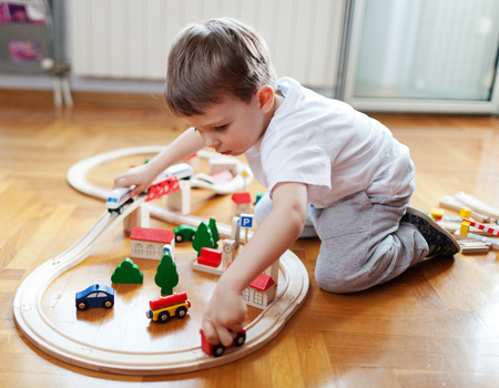 Little boy playing with wooden train set Imagens