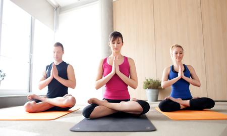 Jonge mensen mediteren in een yogales