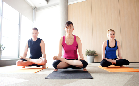 Young people holding a scale pose in a yoga class