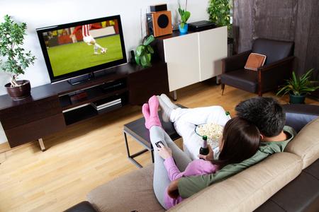 Jong paar ontspannen, tv kijken en met een biertje Stockfoto