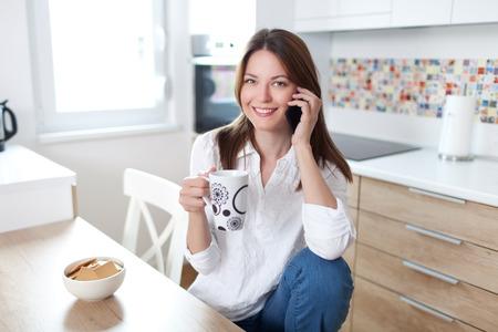 Jonge mooie vrouw met behulp van mobiele telefoon en een kopje koffie in de keuken