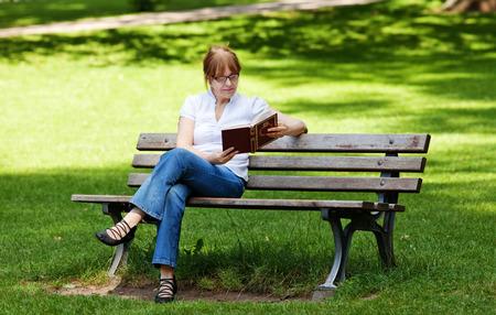 수석 여성이 책을 즐기고 공원에 앉아