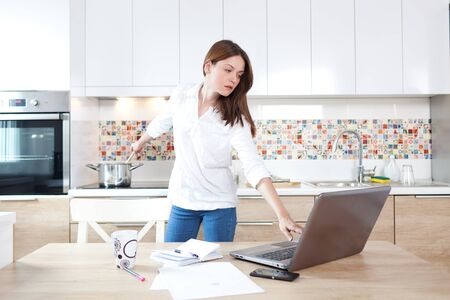 Beautiful young woman working on laptop and cooking at the same time Standard-Bild
