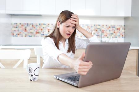 Young woman having trouble with laptop Foto de archivo