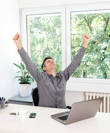 Image of a ecstatic young man sitting at desk 免版税图像
