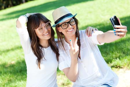 Twee mooie jonge vrouwen die zelfportret outdoor Stockfoto
