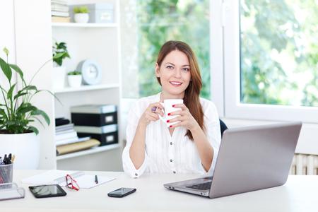 Beautiful young woman having a coffee break in office