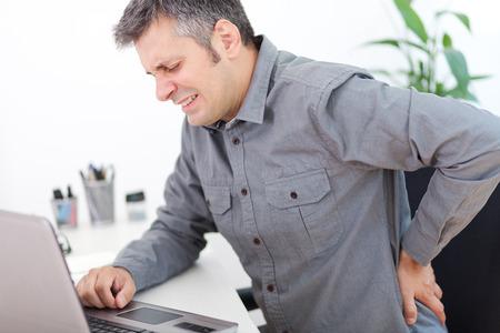 작업 책상에 앉아있는 동안 허리 통증을 가진 젊은 남자의 이미지
