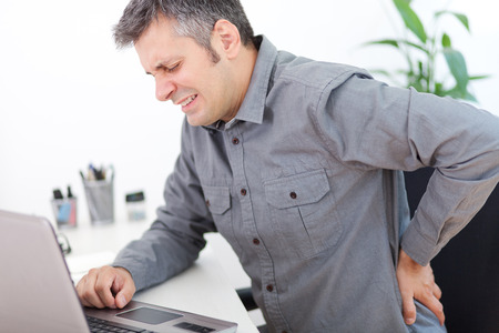 Image of a young man having a back pain while sitting at the working desk 版權商用圖片 - 43001190