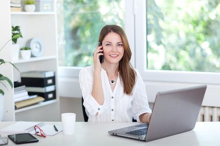 아름 다운 젊은 여자 컴퓨터에서 작동 하 고 전화에 얘기
