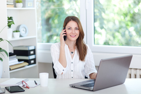 Beautiful young woman working on computer and talking on phone