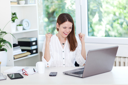 Image of a ecstatic young woman sitting at desk