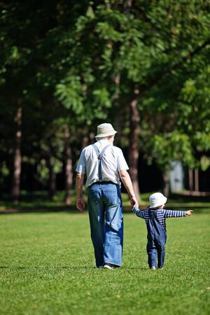 Little boy with his grandpa walking in the park Stock Photo