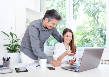 Beautiful young couple in office, using laptop 免版税图像