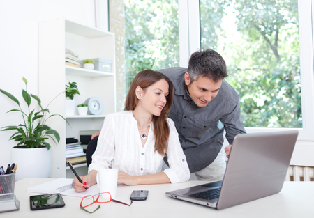 노트북을 사용하는 사무실에서 아름 다운 젊은 부부, 스톡 콘텐츠