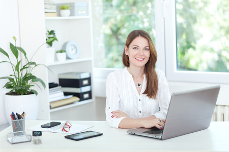 Image of a confident young woman sitting at working desk