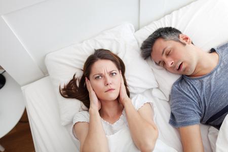 夫のイビキに悩まされ、耳を覆う女