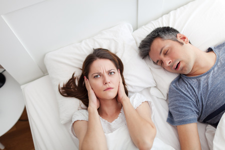 Woman covering ears, annoyed by the snoring of her husband