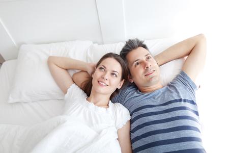 若い夫婦のベッドの上に横たわって、リラックス