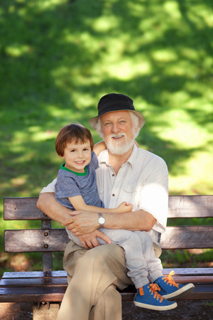 Grandson and grandfather relaxing on the park bench, shallow depth of field