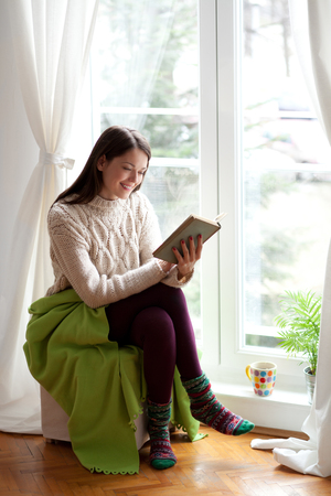 Beautiful young woman sitting by the window reading a book 免版税图像 - 47632139