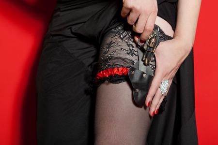 Vrouw nemen klein pistool uit holster Stockfoto