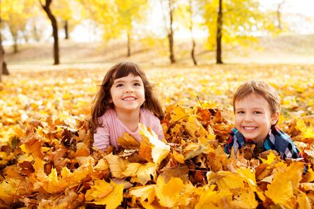 Image of beautiful boy and girl in the pile of autumn leaves, shallow depth of field 免版税图像 - 48315930