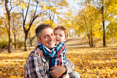 Father and son hugging in autumn park, shallow depth of field