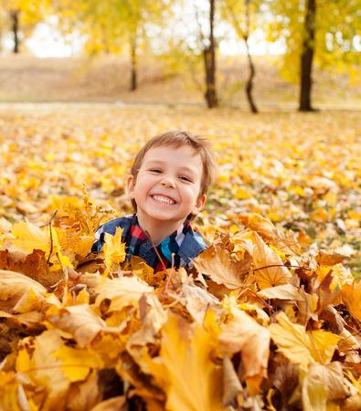 Afbeelding van de mooie jongen in de stapel van de herfst bladeren, ondiepe scherptediepte