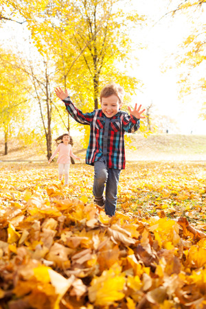 Image of beautiful boy jumping in the pile of autumn leaves, shallow depth of field