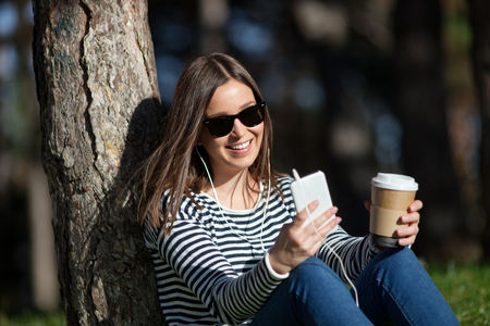 Beautiful young woman listening to music and having takeaway coffee outdoors