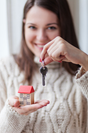 Image of happy young smiling and holding key ring and a miniature model house, shallow depth of field focus on foreground Archivio Fotografico