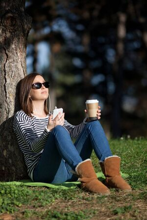 Beautiful young woman listening to music and having takeaway coffee outdoors Reklamní fotografie