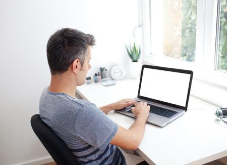 Image d'un jeune homme à un bureau d'ordinateur, travaillant sur ordinateur portable Banque d'images