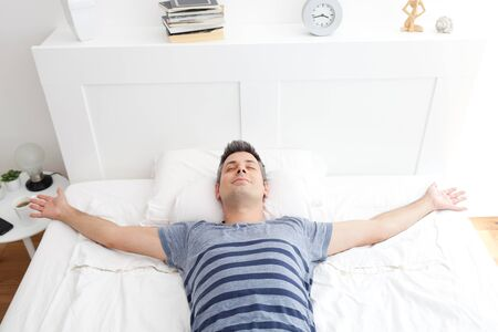 Young man lying on bed, relaxing