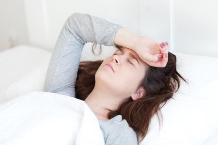 Jonge vrouw ligt ziek in bed met hoofdpijn
