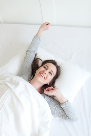 Young beautiful, woman waking up fully rested. Фото со стока