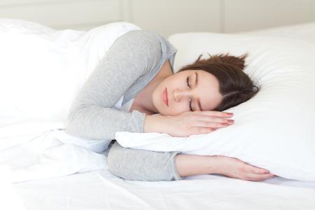 Beautiful young woman asleep, on white background Standard-Bild