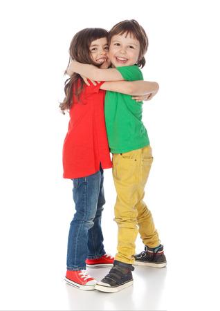 Schattige jongen en meisje knuffelen, geïsoleerd op wit Stockfoto