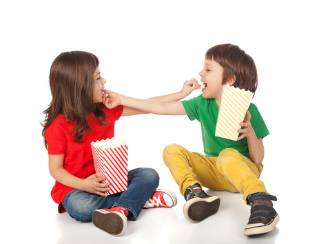 Adorable boy and girl having great time eating popcorn, isolated on white