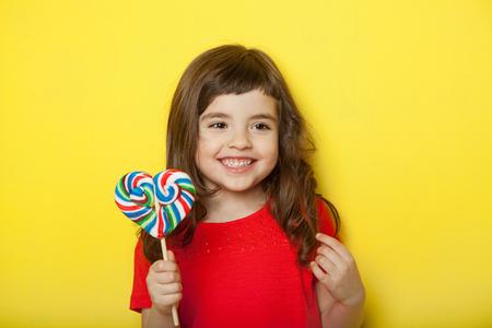 Adorable girl licking lollipop, on yellow background 免版税图像