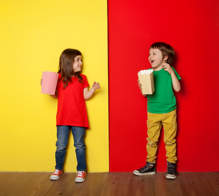 Adorable boy and girl having great time eating popcorn, on red and yellow background Archivio Fotografico