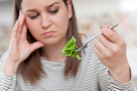 Displeased young woman eating green leaf lettuce. Shallow depth of field, focus on foreground Stock Photo