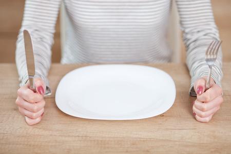 빈 접시에 앉아 불쾌 젊은 여자.