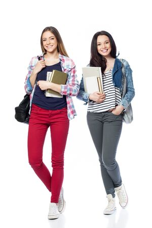 Young female students standing with books and bags, isolated on white 免版税图像