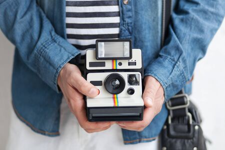 Image of young man holding instant camera and taking picture